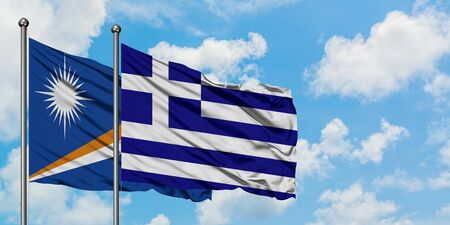 Marshall Islands and Greece flag waving in the wind against white cloudy blue sky together. Diplomacy concept, international relations.