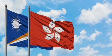 Marshall Islands and Hong Kong flag waving in the wind against white cloudy blue sky together. Diplomacy concept, international relations.