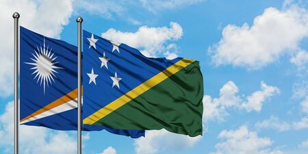 Marshall Islands and Solomon Islands flag waving in the wind against white cloudy blue sky together. Diplomacy concept, international relations. Stok Fotoğraf