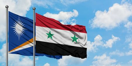 Marshall Islands and Syria flag waving in the wind against white cloudy blue sky together. Diplomacy concept, international relations.