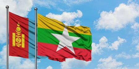 Mongolia and Myanmar flag waving in the wind against white cloudy blue sky together. Diplomacy concept, international relations.