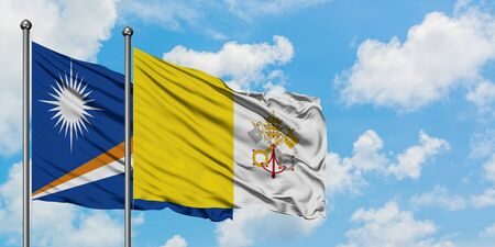 Marshall Islands and Vatican City flag waving in the wind against white cloudy blue sky together. Diplomacy concept, international relations.