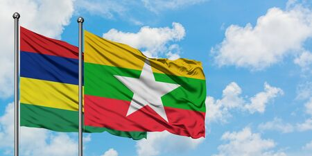 Mauritius and Myanmar flag waving in the wind against white cloudy blue sky together. Diplomacy concept, international relations.