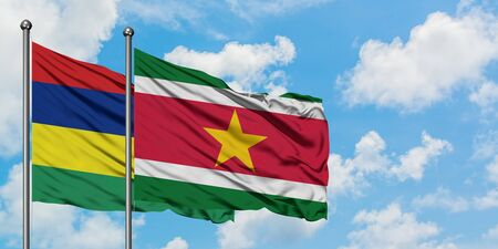 Mauritius and Suriname flag waving in the wind against white cloudy blue sky together. Diplomacy concept, international relations.