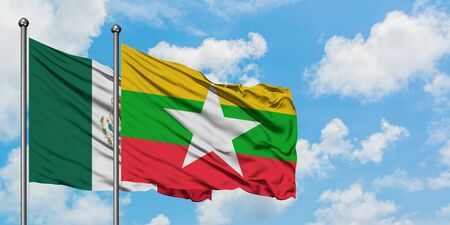 Mexico and Myanmar flag waving in the wind against white cloudy blue sky together. Diplomacy concept, international relations. Stok Fotoğraf