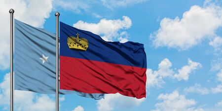 Micronesia and Liechtenstein flag waving in the wind against white cloudy blue sky together. Diplomacy concept, international relations.