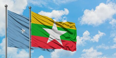 Micronesia and Myanmar flag waving in the wind against white cloudy blue sky together. Diplomacy concept, international relations.