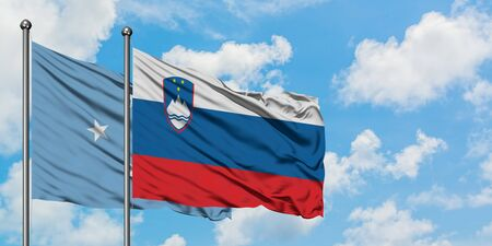 Micronesia and Slovenia flag waving in the wind against white cloudy blue sky together. Diplomacy concept, international relations.