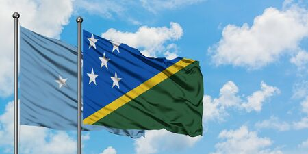 Micronesia and Solomon Islands flag waving in the wind against white cloudy blue sky together. Diplomacy concept, international relations. Stok Fotoğraf