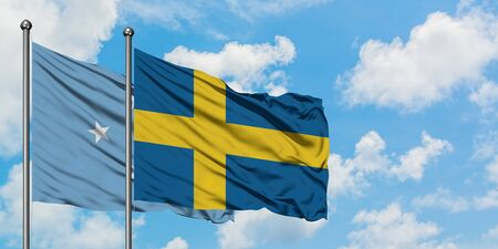 Micronesia and Sweden flag waving in the wind against white cloudy blue sky together. Diplomacy concept, international relations.