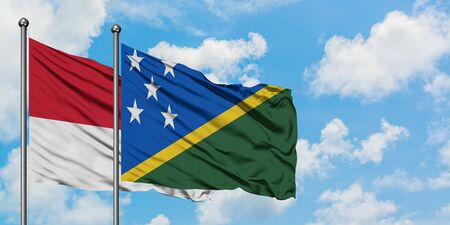 Monaco and Solomon Islands flag waving in the wind against white cloudy blue sky together. Diplomacy concept, international relations.