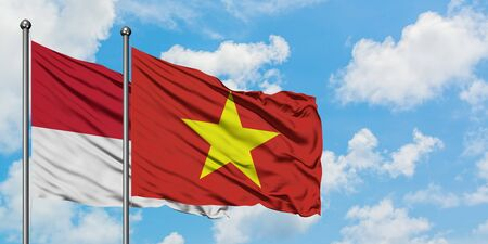 Monaco and Vietnam flag waving in the wind against white cloudy blue sky together. Diplomacy concept, international relations.