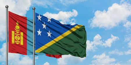 Mongolia and Solomon Islands flag waving in the wind against white cloudy blue sky together. Diplomacy concept, international relations.