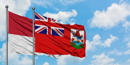 Monaco and Bermuda flag waving in the wind against white cloudy blue sky together. Diplomacy concept, international relations.