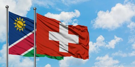 Namibia and Switzerland flag waving in the wind against white cloudy blue sky together. Diplomacy concept, international relations.