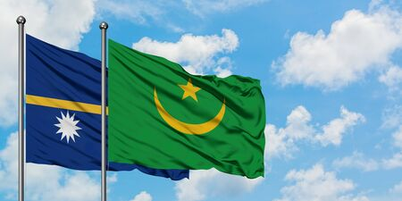 Nauru and Mauritania flag waving in the wind against white cloudy blue sky together. Diplomacy concept, international relations. Фото со стока