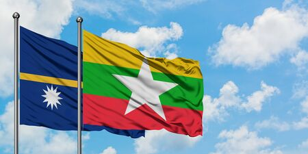 Nauru and Myanmar flag waving in the wind against white cloudy blue sky together. Diplomacy concept, international relations.