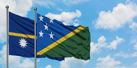 Nauru and Solomon Islands flag waving in the wind against white cloudy blue sky together. Diplomacy concept, international relations.