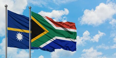 Nauru and South Africa flag waving in the wind against white cloudy blue sky together. Diplomacy concept, international relations.
