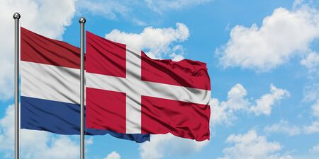 Netherlands and Denmark flag waving in the wind against white cloudy blue sky together. Diplomacy concept, international relations. Archivio Fotografico