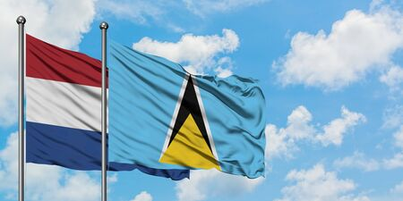 Netherlands and Saint Lucia flag waving in the wind against white cloudy blue sky together. Diplomacy concept, international relations.