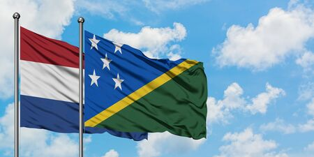 Netherlands and Solomon Islands flag waving in the wind against white cloudy blue sky together. Diplomacy concept, international relations. Stok Fotoğraf