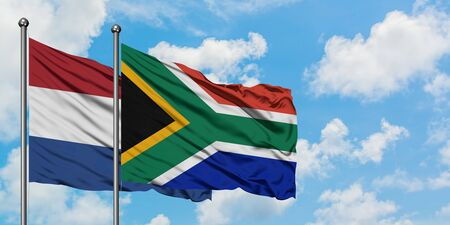 Netherlands and South Africa flag waving in the wind against white cloudy blue sky together. Diplomacy concept, international relations.