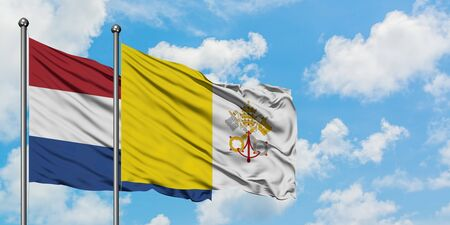 Netherlands and Vatican City flag waving in the wind against white cloudy blue sky together. Diplomacy concept, international relations.