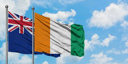 New Zealand and Cote D'Ivoire flag waving in the wind against white cloudy blue sky together. Diplomacy concept, international relations.