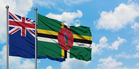 New Zealand and Dominica flag waving in the wind against white cloudy blue sky together. Diplomacy concept, international relations.