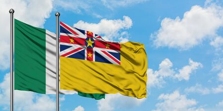 Nigeria and Niue flag waving in the wind against white cloudy blue sky together. Diplomacy concept, international relations.