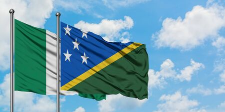 Nigeria and Solomon Islands flag waving in the wind against white cloudy blue sky together. Diplomacy concept, international relations.