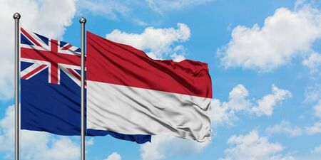 New Zealand and Indonesia flag waving in the wind against white cloudy blue sky together. Diplomacy concept, international relations.