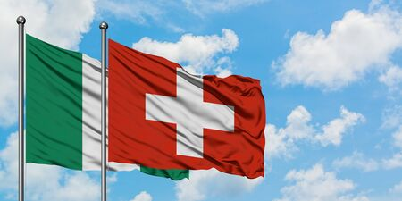 Nigeria and Switzerland flag waving in the wind against white cloudy blue sky together. Diplomacy concept, international relations.