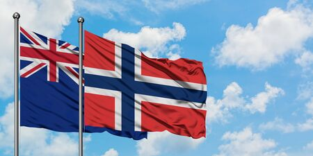 New Zealand and Norway flag waving in the wind against white cloudy blue sky together. Diplomacy concept, international relations.