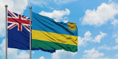 New Zealand and Rwanda flag waving in the wind against white cloudy blue sky together. Diplomacy concept, international relations.
