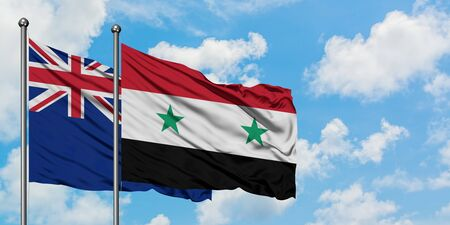 New Zealand and Syria flag waving in the wind against white cloudy blue sky together. Diplomacy concept, international relations. Banco de Imagens