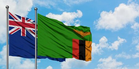 New Zealand and Zambia flag waving in the wind against white cloudy blue sky together. Diplomacy concept, international relations.