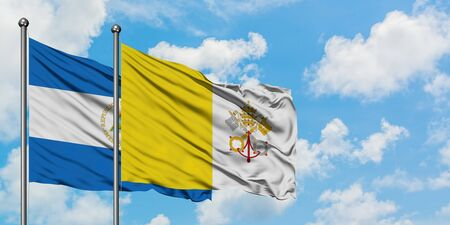 Nicaragua and Vatican City flag waving in the wind against white cloudy blue sky together. Diplomacy concept, international relations.