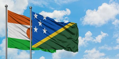 Niger and Solomon Islands flag waving in the wind against white cloudy blue sky together. Diplomacy concept, international relations.