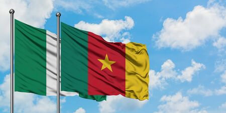 Nigeria and Cameroon flag waving in the wind against white cloudy blue sky together. Diplomacy concept, international relations. Imagens