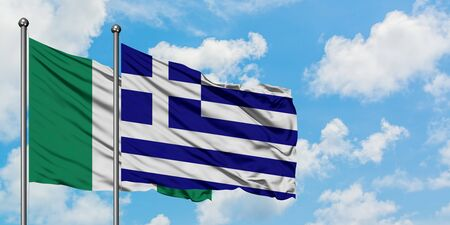 Nigeria and Greece flag waving in the wind against white cloudy blue sky together. Diplomacy concept, international relations. Standard-Bild