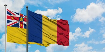 Niue and Romania flag waving in the wind against white cloudy blue sky together. Diplomacy concept, international relations.