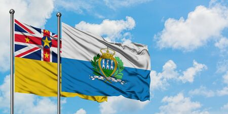 Niue and San Marino flag waving in the wind against white cloudy blue sky together. Diplomacy concept, international relations.