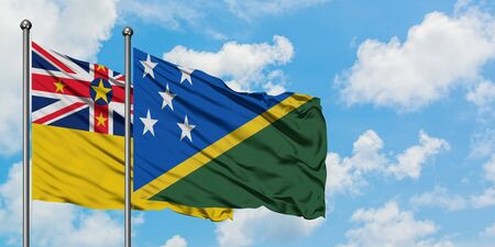 Niue and Solomon Islands flag waving in the wind against white cloudy blue sky together. Diplomacy concept, international relations. Stok Fotoğraf