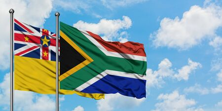 Niue and South Africa flag waving in the wind against white cloudy blue sky together. Diplomacy concept, international relations.