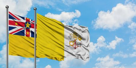 Niue and Vatican City flag waving in the wind against white cloudy blue sky together. Diplomacy concept, international relations.