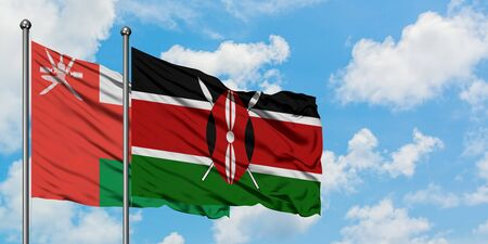 Oman and Kenya flag waving in the wind against white cloudy blue sky together. Diplomacy concept, international relations.