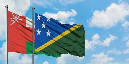 Oman and Solomon Islands flag waving in the wind against white cloudy blue sky together. Diplomacy concept, international relations.