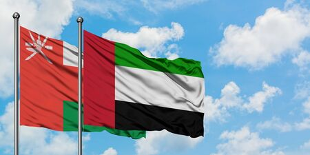 Oman and United Arab Emirates flag waving in the wind against white cloudy blue sky together. Diplomacy concept, international relations.